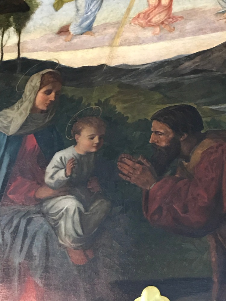 Close up of Jesus sat on Mary's lap with a shepherd adoring him