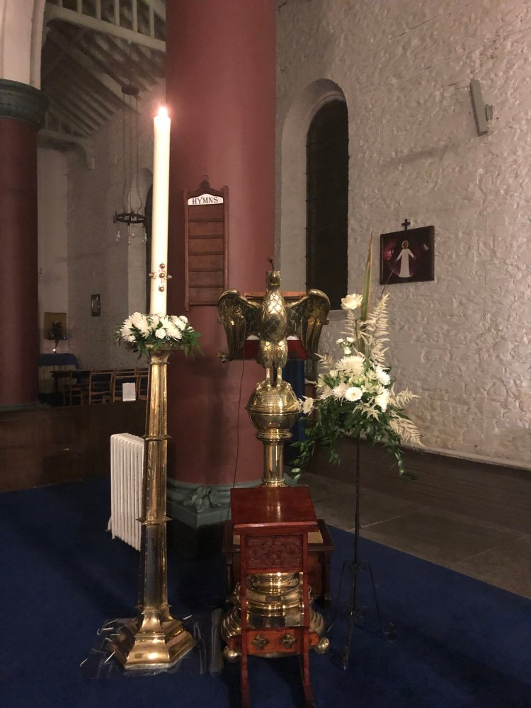 Eagle shaped brass lectern, accompanied by Easter candle and flowers